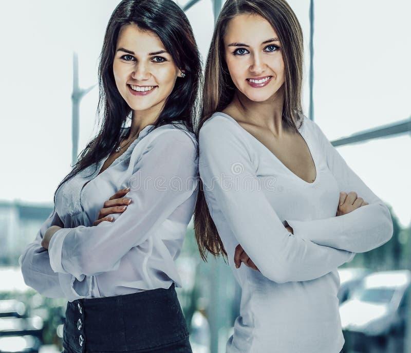 Dos jovenes, cr permanente acertado atractivo de los brazos de la mujer de negocios fotos de archivo libres de regalías