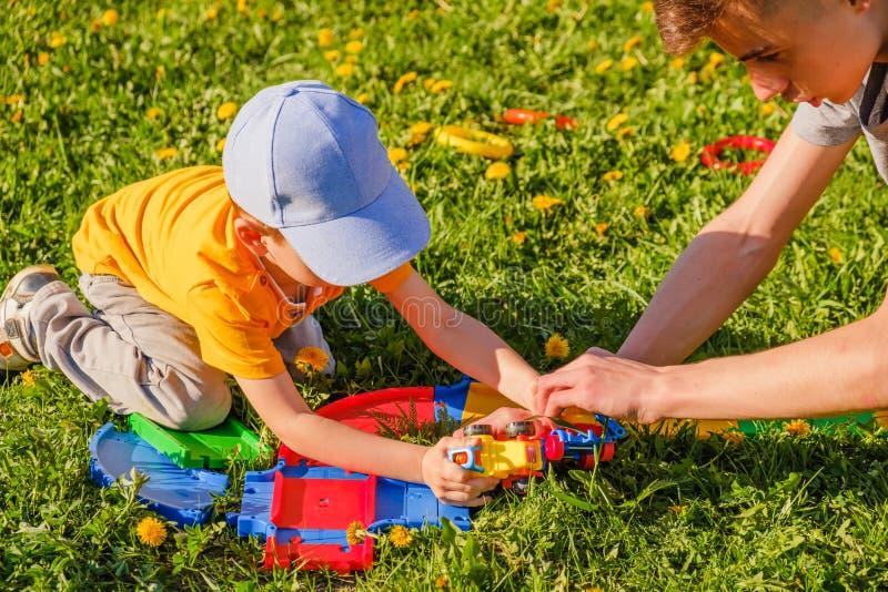 Dos juegos de los hermanos con un coche del juguete en el c?sped de la hierba verde foto de archivo libre de regalías