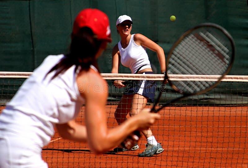 Dos jugadores de tenis de sexo femenino deportivos jovenes que tienen un juego en el sol. imágenes de archivo libres de regalías