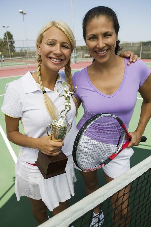 Dos jugadores de tenis de sexo femenino que celebran el trofeo foto de archivo libre de regalías