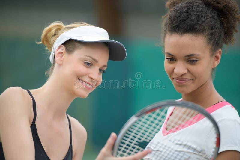 Dos jugadores de tenis que hablan sosteniendo la estafa de tenis fotos de archivo
