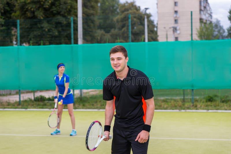 Dos jugadores de tenis que juegan dobles en el campo de tenis imagen de archivo libre de regalías
