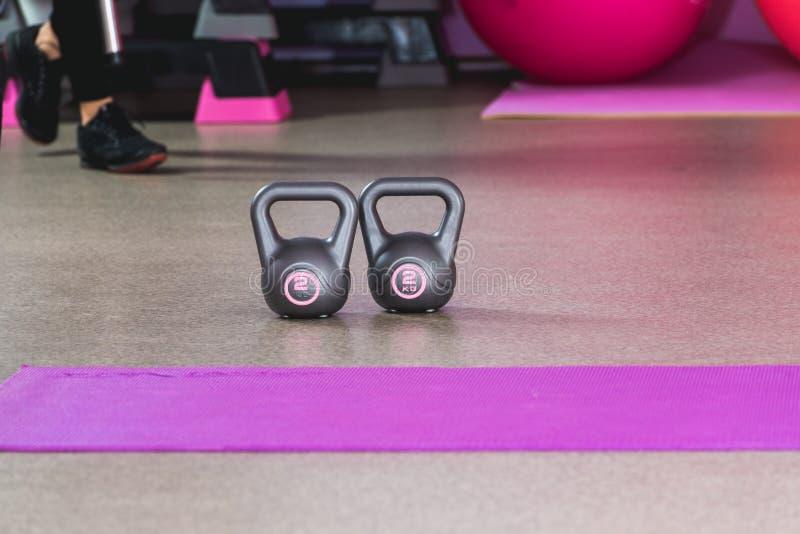 Dos kilos en un gris colorean pesos en un estudio del deporte con las bolas rosadas en el backround y las zapatillas de deporte foto de archivo libre de regalías