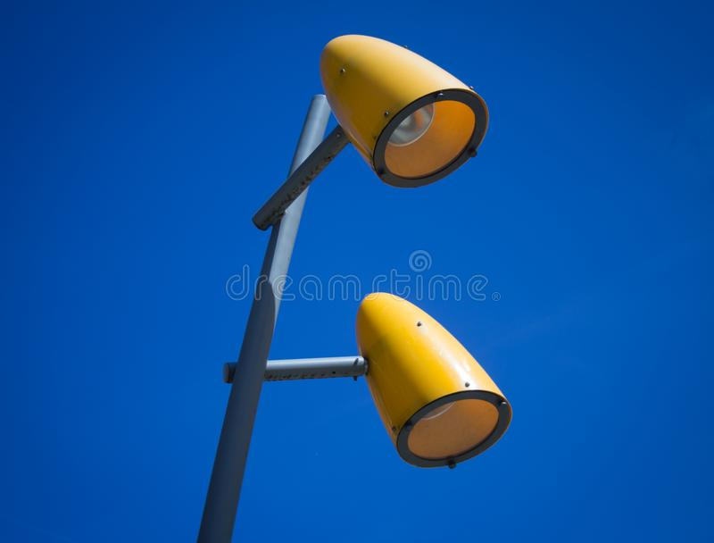 Dos lámparas de calle amarillas con el cielo azul imágenes de archivo libres de regalías