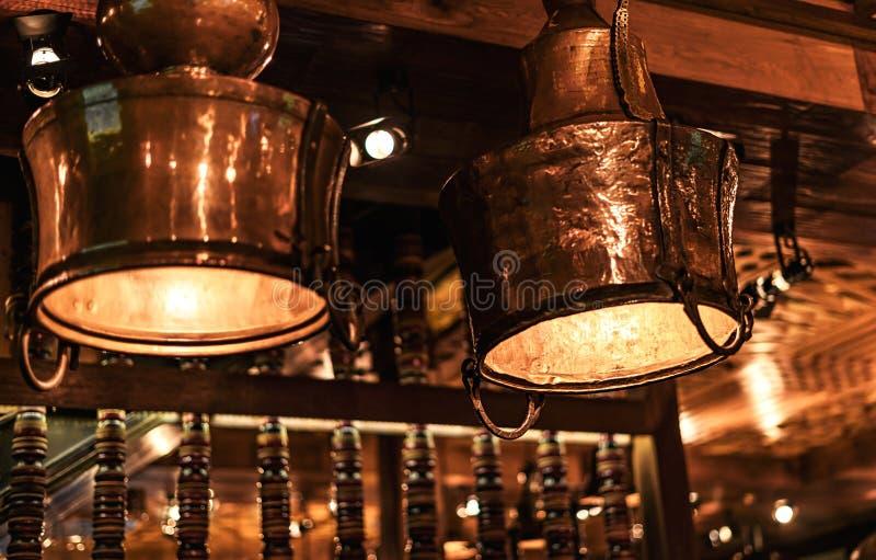 Dos lámparas de cobre amarillo hermosas del vintage en un café fotografía de archivo