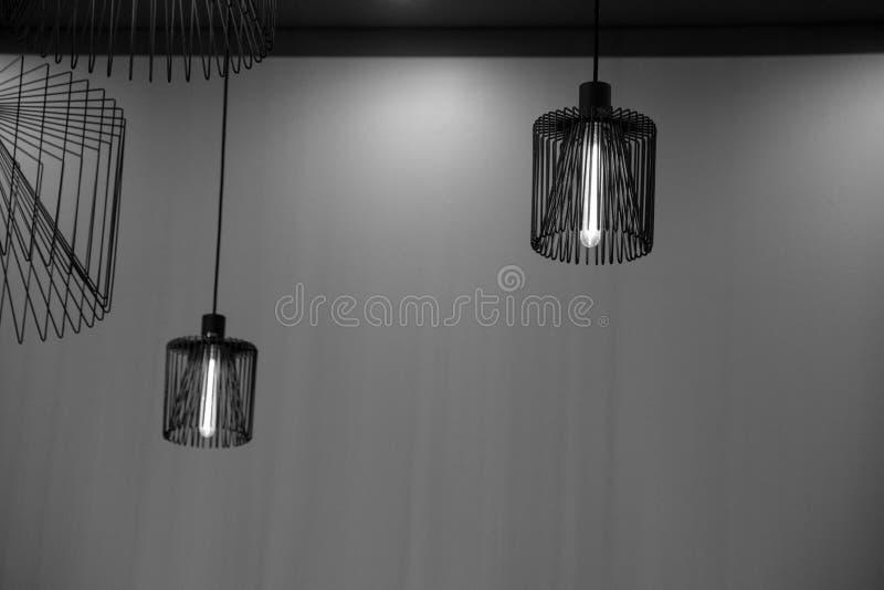 Dos lámparas del alambre de metal están colgando en fondo vacío de la pared imagen de archivo