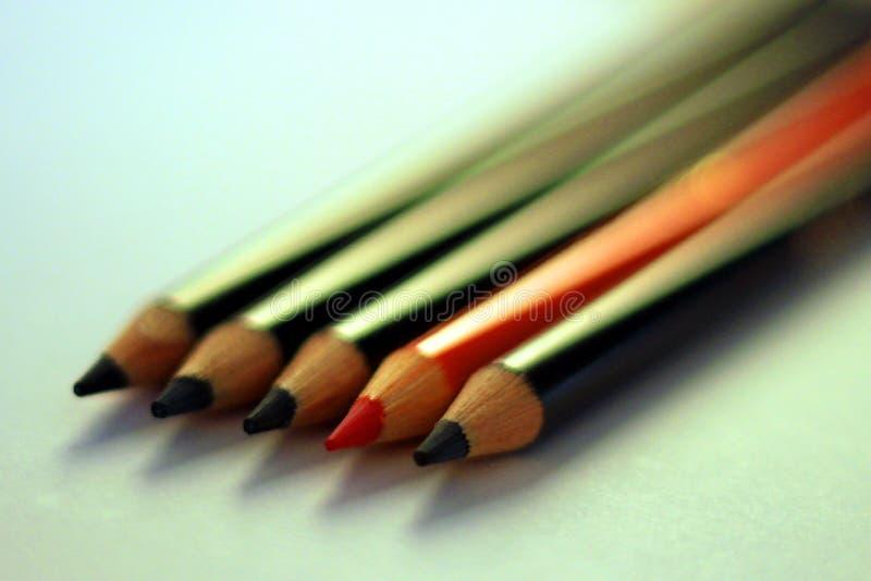 Dos lápices anaranjados entre los lápices negros foto de archivo libre de regalías