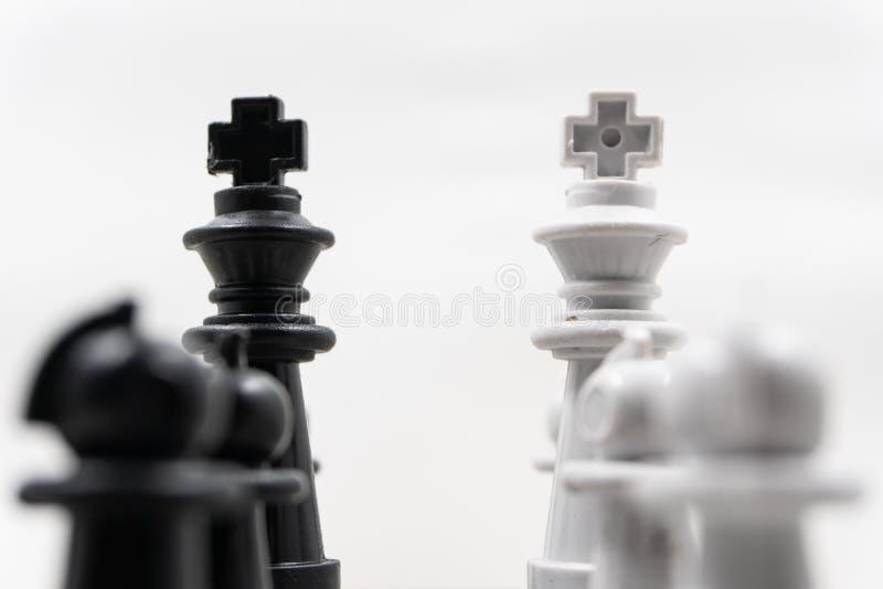 Dos lados de los pedazos de ajedrez con los reyes negros y los reyes blancos y sus empe?os que se hacen frente Hay un fondo blanc foto de archivo libre de regalías