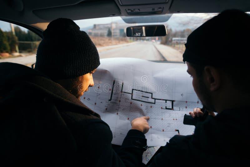 Dos ladrones que planean y que señalan en el mapa del modelo imagenes de archivo