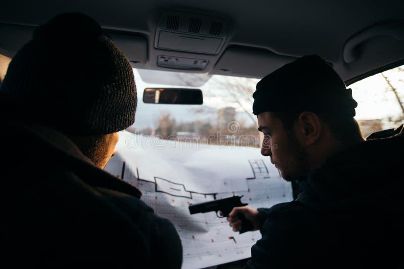 Dos ladrones que planean y que señalan en el mapa del modelo su objetivo mientras que sostiene sus armas foto de archivo libre de regalías