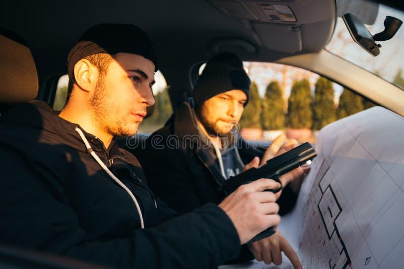 Dos ladrones que planean y que señalan en el mapa del modelo su objetivo mientras que sostiene sus armas foto de archivo