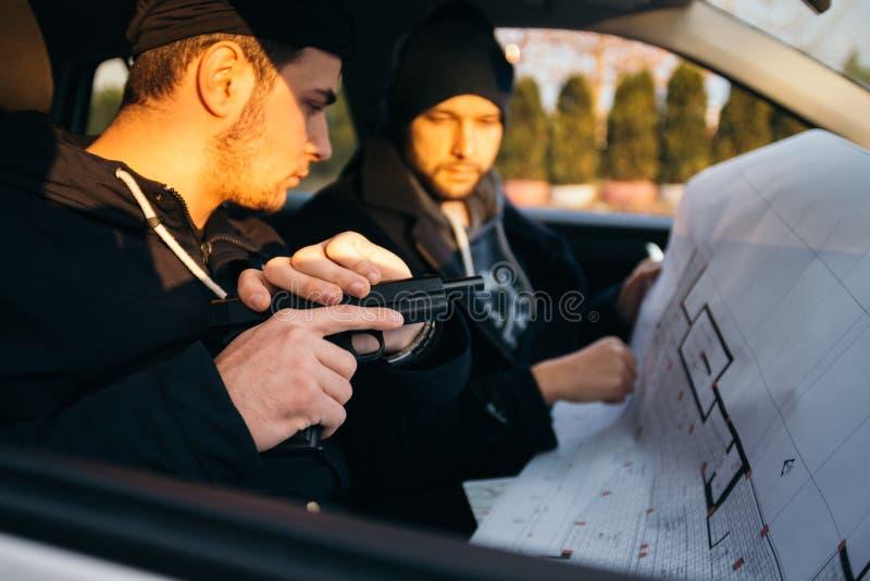 Dos ladrones que planean y que señalan en el mapa del modelo su objetivo mientras que sostiene sus armas imagen de archivo