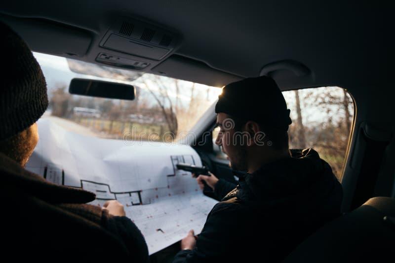 Dos ladrones que planean y que señalan en el mapa del modelo su objetivo mientras que sostiene sus armas fotografía de archivo