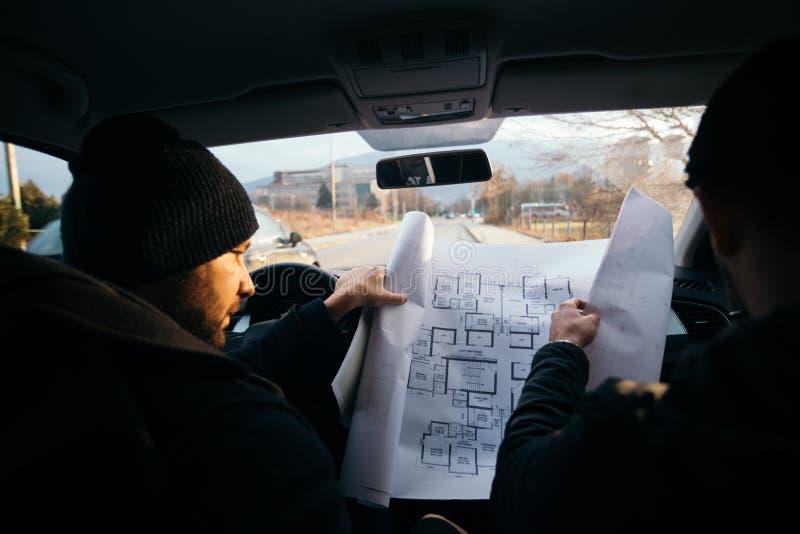 Dos ladrones violentos que se sientan en un coche que mira un modelo del edificio que quieren robar imagen de archivo