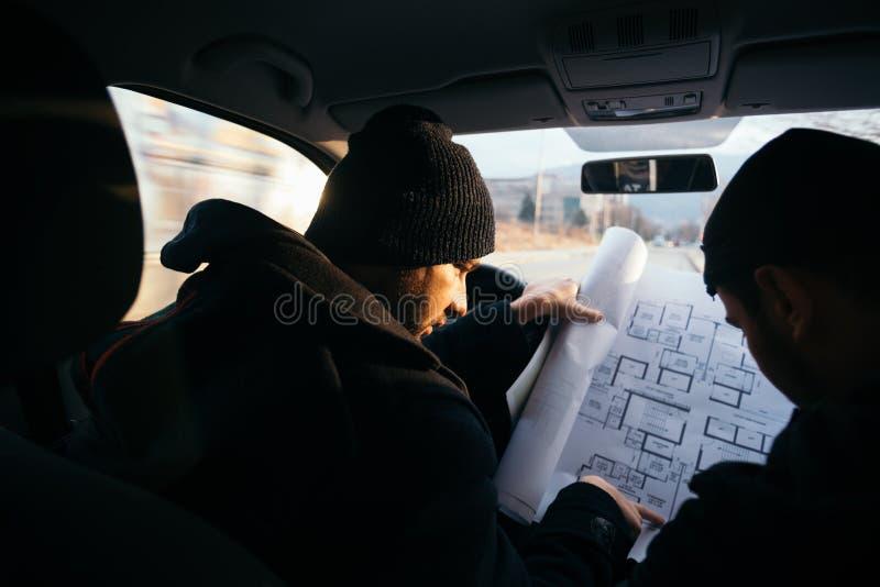 Dos ladrones violentos que se sientan en un coche que mira un modelo del edificio que quieren robar fotos de archivo libres de regalías