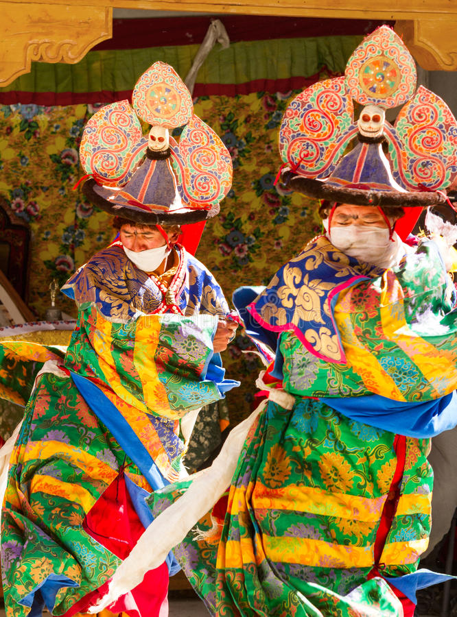 Dos lamas realizan una danza enmascarada y vestida religiosa del sombrero negro del misterio del budismo tibetano fotografía de archivo