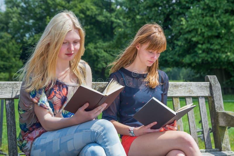 Dos libros de lectura de las muchachas en banco en naturaleza foto de archivo