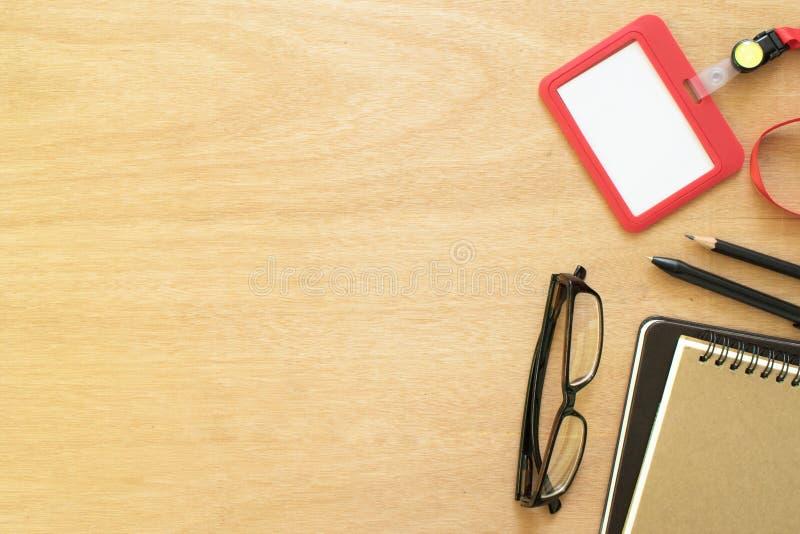 Dos libros, paperclip, lápices, plumas, tarjetas del empleado, y vidrios del ojo en el escritorio de madera marrón rústico Espaci imágenes de archivo libres de regalías