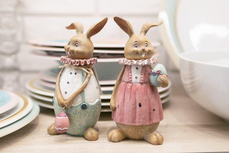Dos liebres de la cerámica de Pascua en un estante de la tabla de cocina Estatuillas de cerámica para servir la tabla festiva Foc fotos de archivo