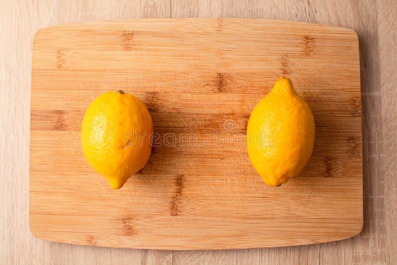 Dos limones en la tabla de cortar de madera fotografía de archivo