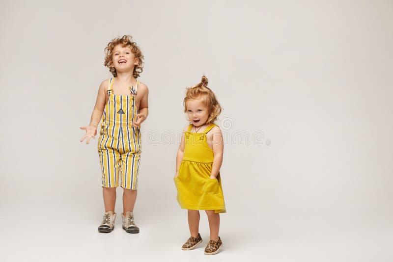 Dos lindos y elegantes niños, niños y niñas con ropa de verano de moda posando en un fondo beige Aislado en su totalidad imagenes de archivo
