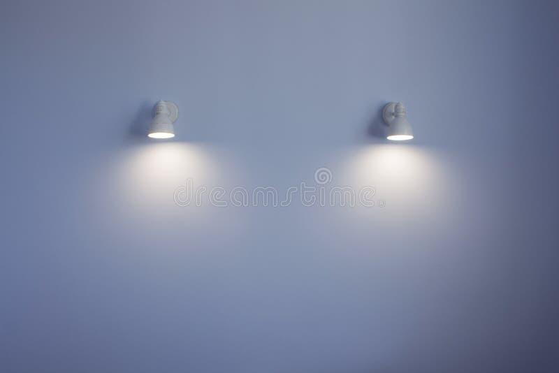 Dos los apliques blancos brillantes en una pared azul fotografía de archivo