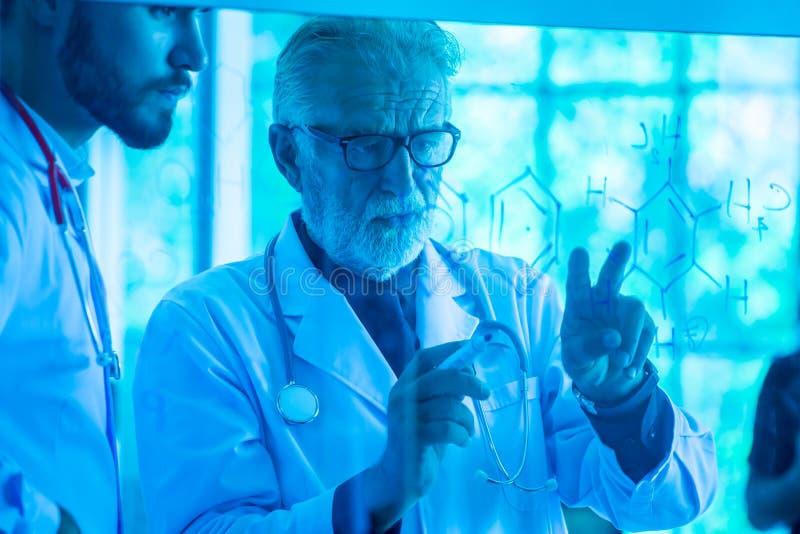Dos médicos de sexo masculino que se consultan en tono azul del tablero de cristal imagen de archivo