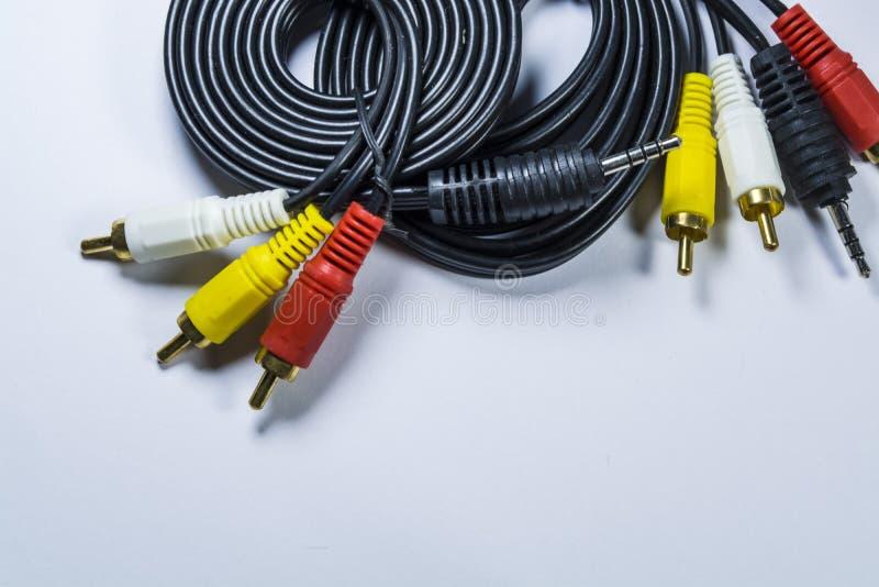 Dos madejas de cables con los enchufes multicolores un tulipán Cuerda negra Fondo monofónico blanco fotos de archivo libres de regalías