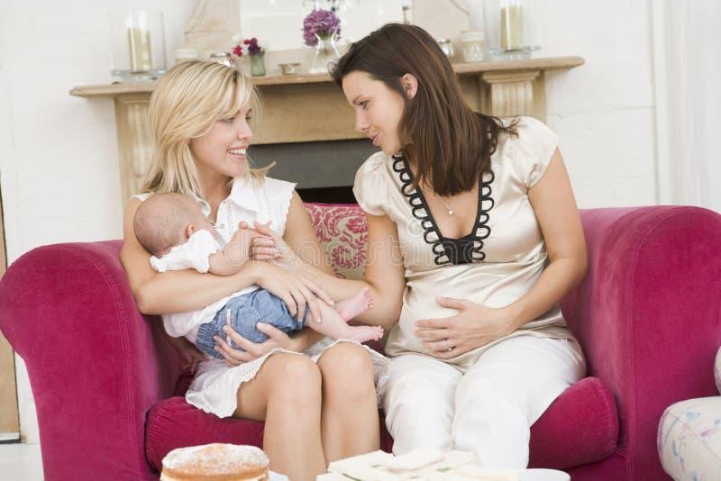 Dos madres en sala de estar con el bebé y la torta imagen de archivo libre de regalías