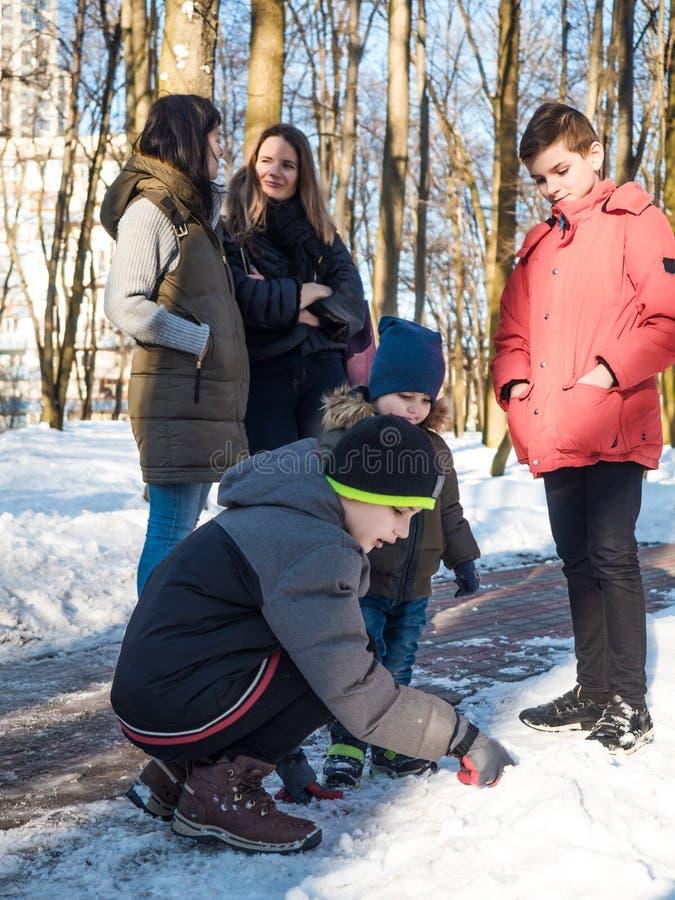 Dos madres que hablan durante su juego de niños con nieve en invierno parquean imagen de archivo libre de regalías