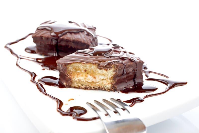 Dos magdalenas del chocolate con el jarabe y la fork foto de archivo