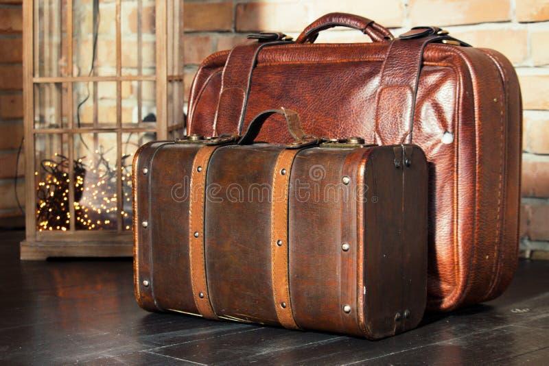 Dos maletas de cuero marrones en piso de madera contra la pared de ladrillo Diseño retro del equipaje Concepto del recorrido y de fotografía de archivo