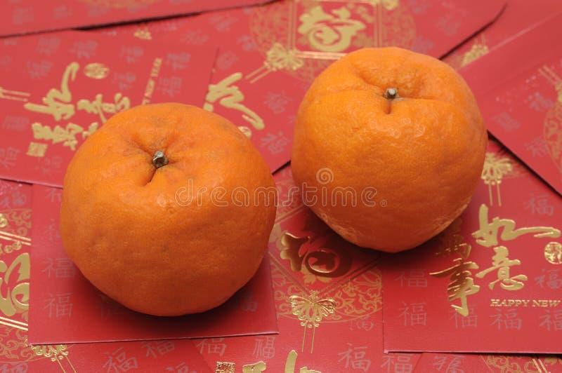 Dos mandarinas en algunos sobres rojos fotos de archivo libres de regalías