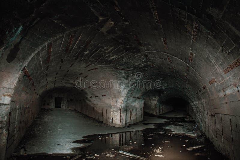 Dos maneras en pasillos o túneles concretos subterráneos largos en arcón abandonada o refugio nuclear imagen de archivo