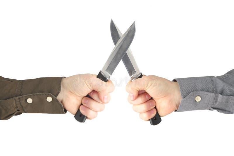 Dos manos con los cuchillos que se hacen frente Confrontación y guerra imagenes de archivo