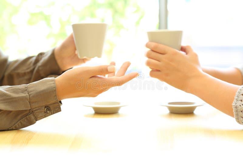 Dos manos de las mujeres que hablan en una barra que sostiene las tazas de café imagen de archivo libre de regalías