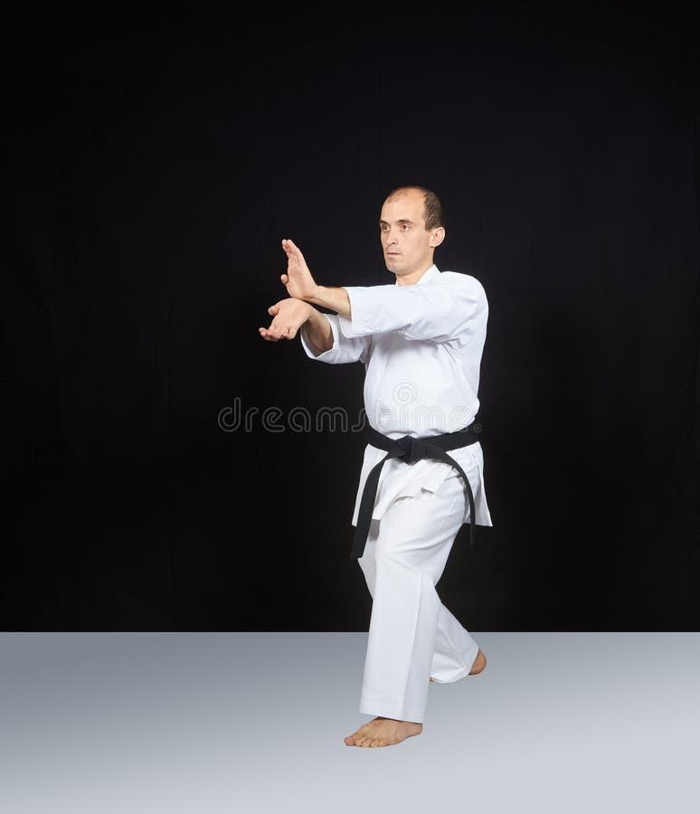 Dos manos de los soplos están entrenando al atleta en una superficie blanca imagenes de archivo