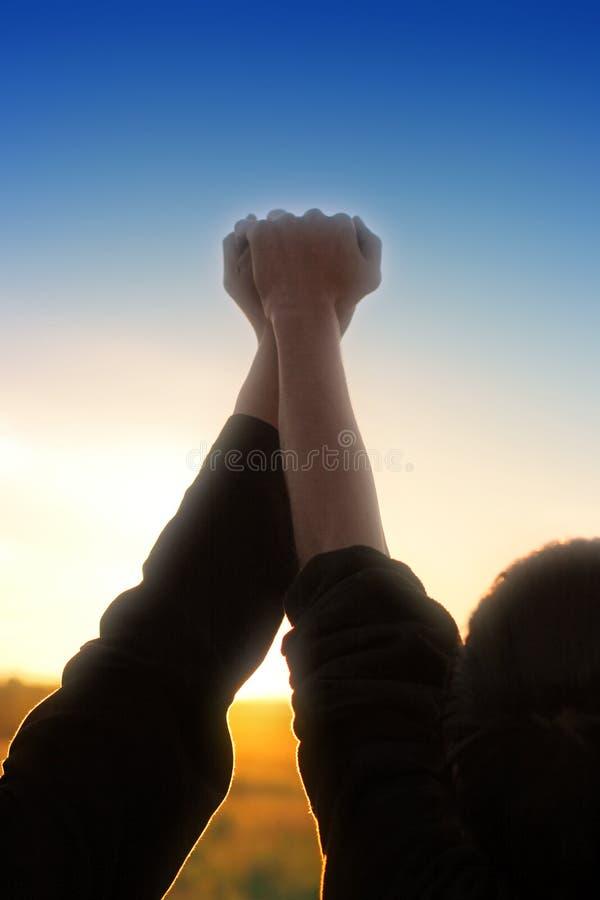 Dos manos en fondo de la puesta del sol imágenes de archivo libres de regalías