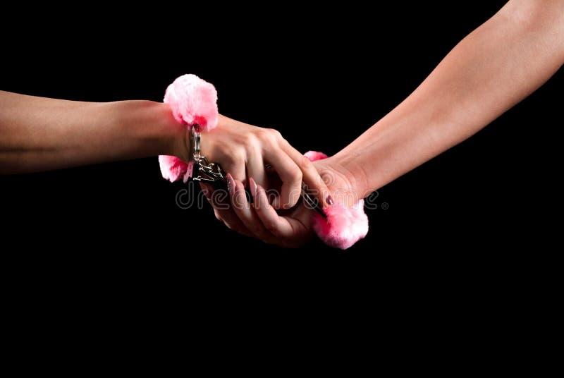 Dos manos femeninas jovenes del control y atado con las esposas foto de archivo libre de regalías