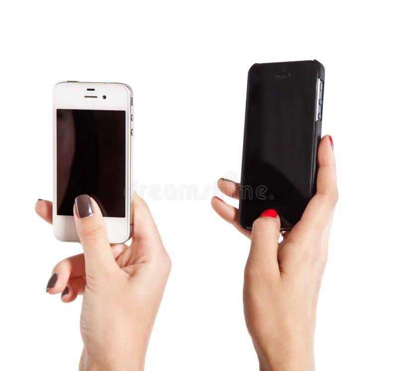 Dos manos femeninas toman las fotos en los teléfonos móviles fotos de archivo