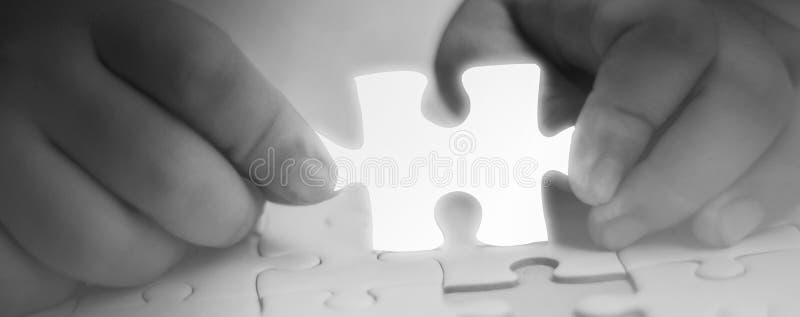 Dos manos que llevan a cabo componentes que falta del pedazo del tono blanco del pedazo del rompecabezas que brillan intensamente imagenes de archivo