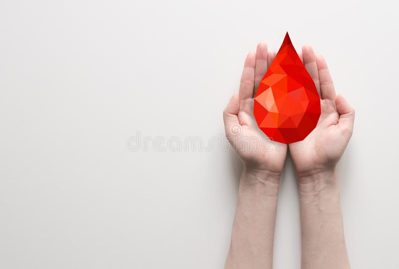 Dos manos que llevan a cabo gota de sangre poligonal roja fotos de archivo