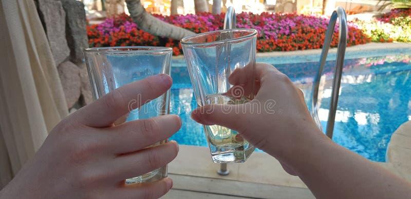 Dos manos que sostienen los vidrios con la vid blanca juntos sobre piscina azul imagen de archivo