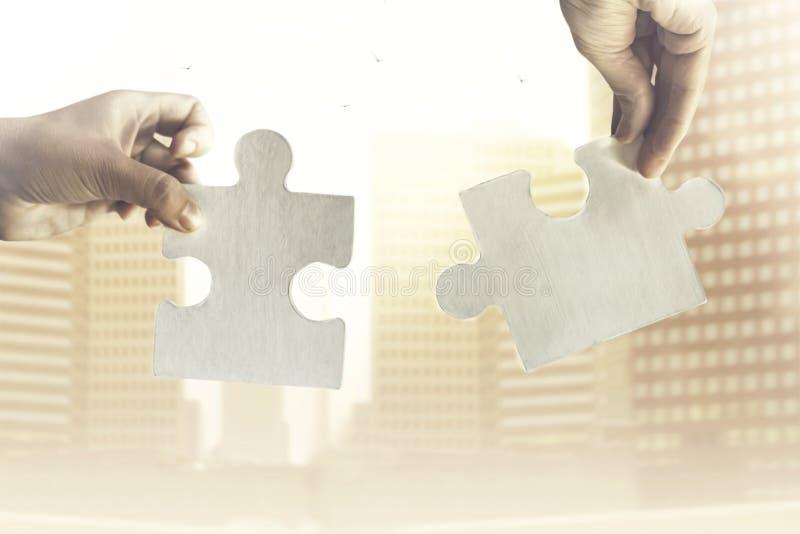 Dos manos se unen a juntos dos pedazos de rompecabezas, de concepto de estrategia y de negocio imagen de archivo