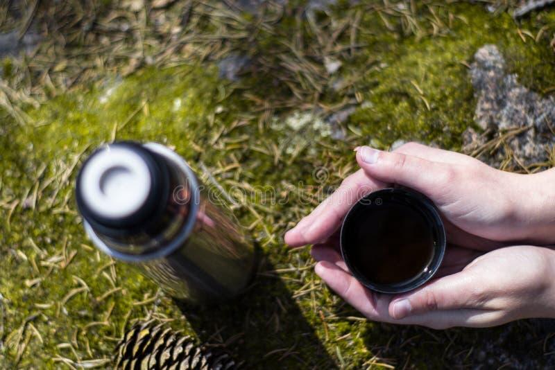 Dos manos sostienen la taza de t? o de caf? caliente en roca cubierta de musgo imágenes de archivo libres de regalías