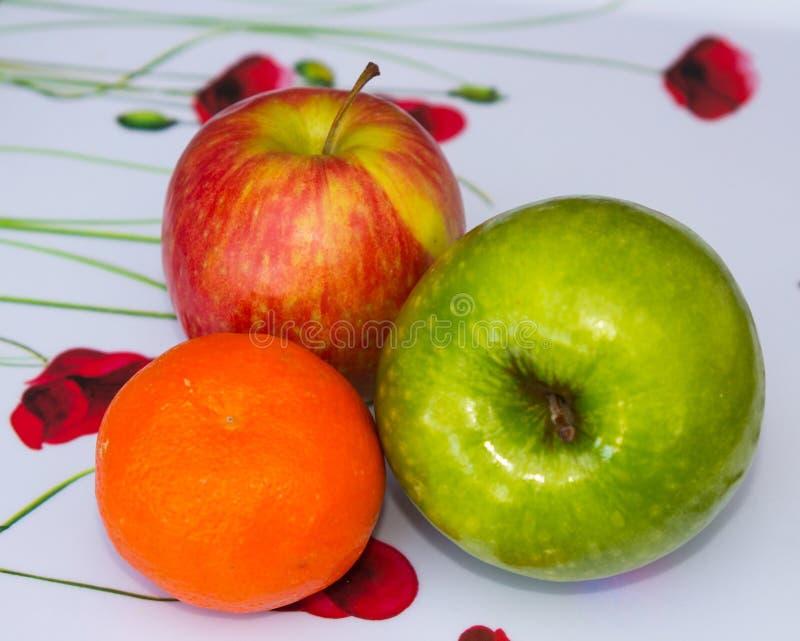 Dos manzanas y una pequeña mandarina que son parte de una tienda de ultramarinos semanal proporcionan un elemento esencial de los fotos de archivo libres de regalías