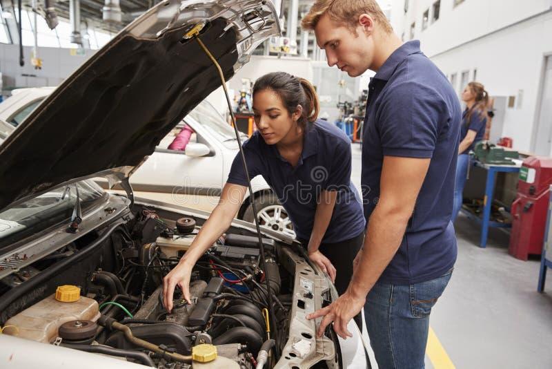 Dos mecánicos del aprendiz que miran el motor en un coche foto de archivo libre de regalías