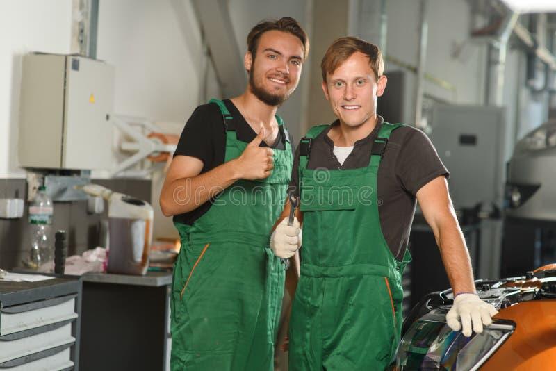 Dos mecánicos jovenes se colocan cerca del coche en guardapolvos verdes en fotos de archivo