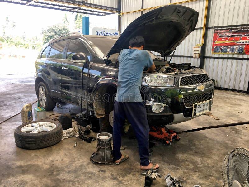 Dos mecánicos locales están intentando fijar el coche de Checrolet SUV en Bangk fotografía de archivo libre de regalías