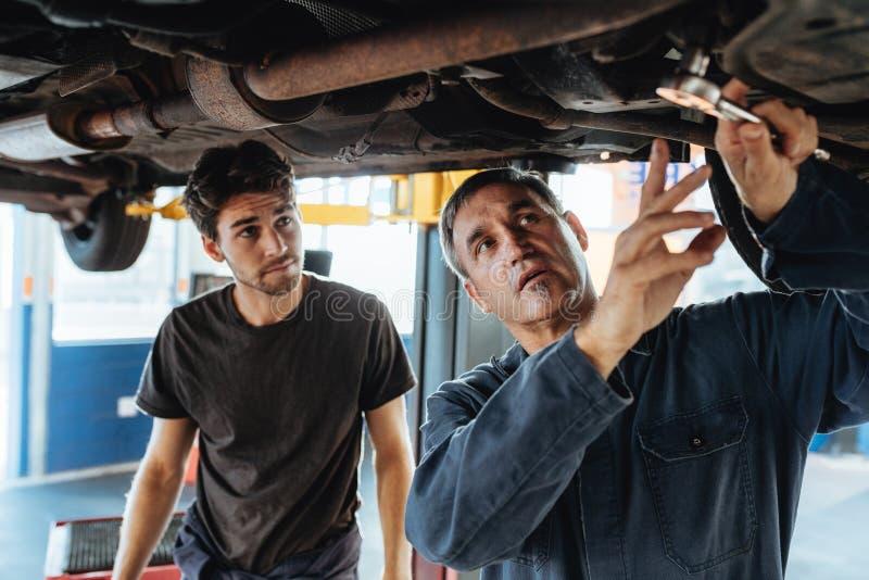 Dos mecánicos que reparan un coche fotos de archivo libres de regalías